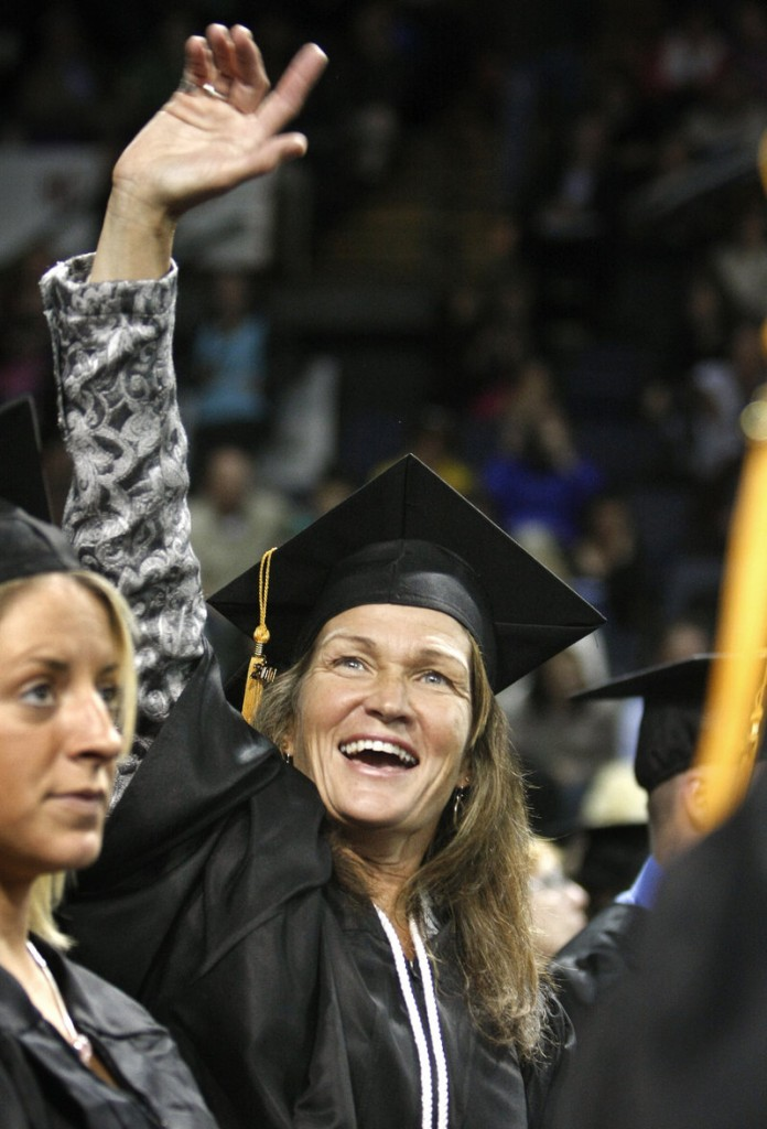 Kelly Akerley of North Bridgton looks for her family as she celebrates receiving her bachelor's degree in health sciences at the University of Southern Maine's 131st commencement at the Cumberland County Civic Center in Portland on Saturday.