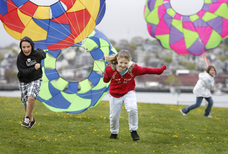 Sara Watkins, 9, center, of Plaistow, N.H., pulls a kite bol to the finish line, closely followed by 11-year-old Jacob Marcous, left, of Norway.