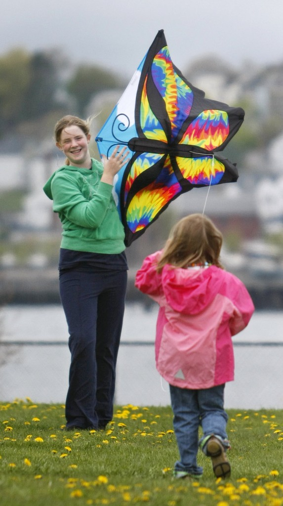 Allyson Molloy, 13, of Portland helps her cousin, Sarah Sweeney, 6, of Massachusetts, launch her butterfly kite.