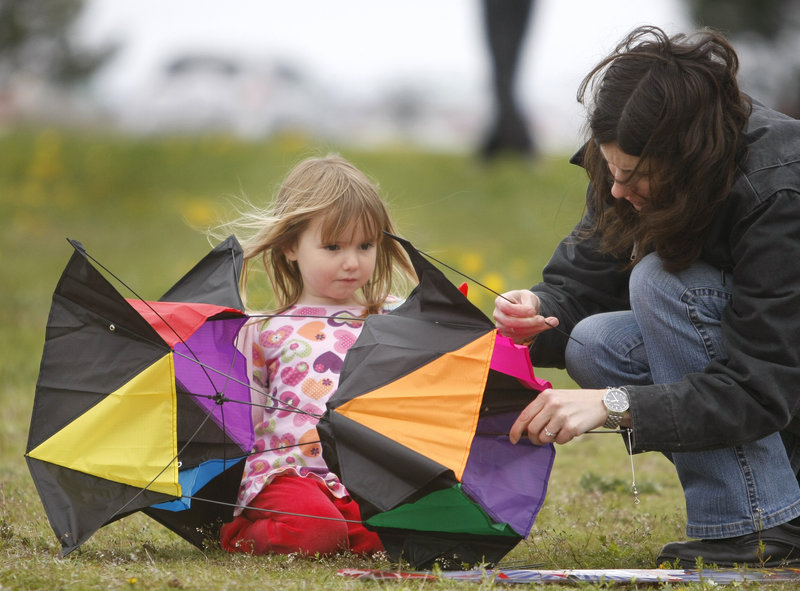 Four-year-old Erica Roussel and her mom, Lanelle Roussel, of Falmouth, assemble a box kite at the Bug Light Kite Festival Saturday in South Portland.