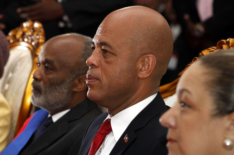 Haiti's incoming President Michel Martelly, center, outgoing President Rene Preval, left, and Martelly's wife, Sophia, sit during Martelly's ceremony in Port-au-Prince on Saturday.