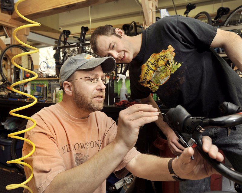 Chris Porter, right, service manager at CycleMania in Portland, guides reporter Ray Routhier as he attaches a new brake cable to a bike.