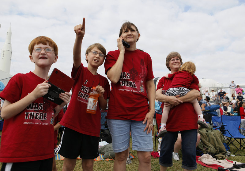 Adam Wheeler, 8, Ryan Wheeler, 11, Debbie Wheeler and Pegy Looten holding Erin Wheeler, all of Bowie, Md., watch the space shuttle from the Kennedy Space Center Visitors Complex in Cape Canaveral, Fla., on Monday.
