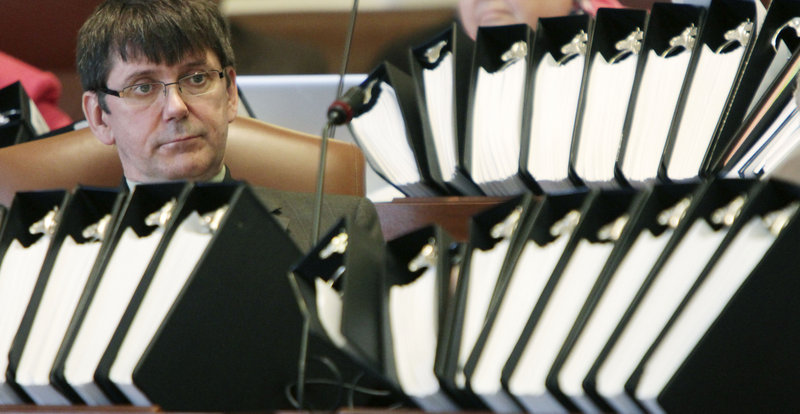 Behind binders of papers, Sen. John Patrick, D-Rumford, listens to debate Monday on the health insurance overhaul.
