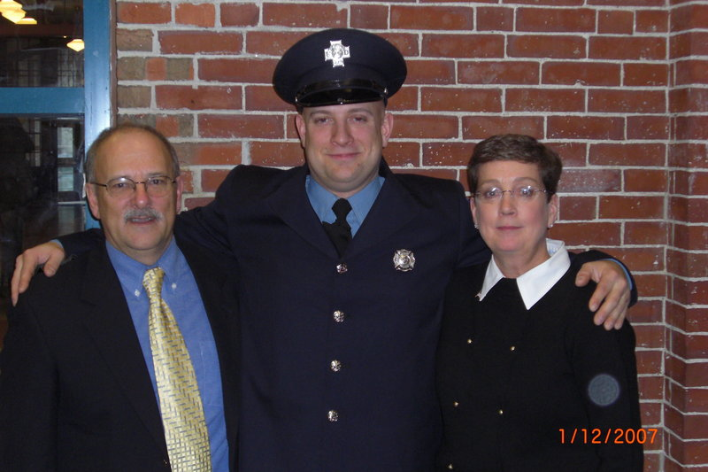 Mary Corbin, right, with her husband, John, and son Joshua at his fire department drill school graduation.