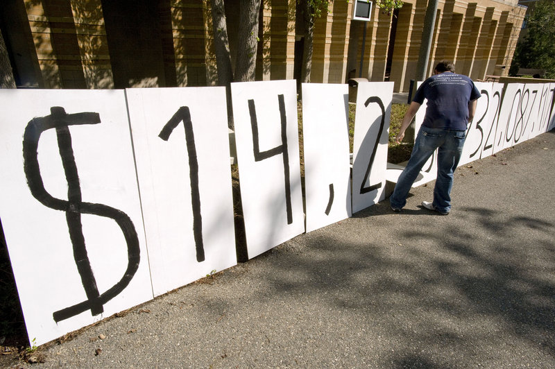 """Adam Weinberg, a member of Young Americans for Liberty, resets numbers on a national debt clock in Irvine,Calif., in April. If Congress doesn't end its standoff and raise the debt ceiling beyond $14.3 trillion, the govern-ment could default. """"In the economic area, this is the equivalent of nuclear war,"""" says analyst Edward Knight."""