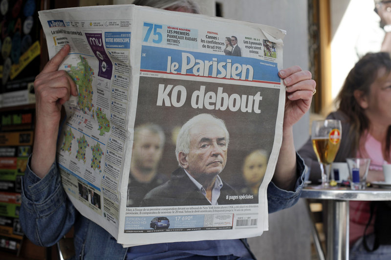 A woman reads the French newspaper Le Parisien, with a headline about the arrest on sexual assault charges of Dominique Strauss-Kahn, the head of the International Monetary Fund, in Paris on Tuesday. Strauss-Kahn had been considered a possible contender for French president.