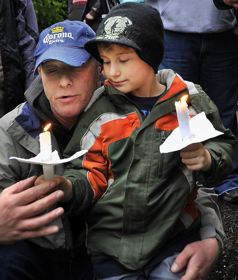 Jay Wilcox of Sanford and his son, Travis, 7, were among about 400 people who attended a South Berwick vigil Tuesday for an unidentified boy whose body was found in the woods there.