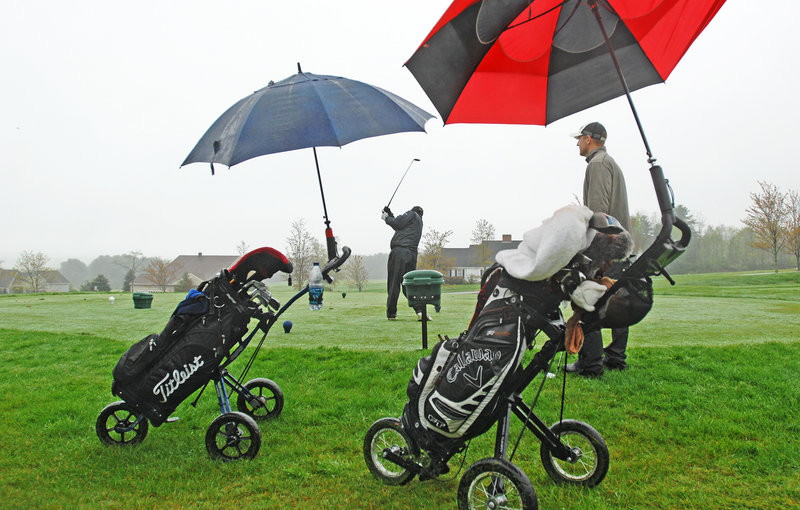 Frank Neuts of Portland hits a shot as Travis Ferrante watches Wednesday at a soggy Falmouth Country Club. They enjoy playing golf in the rain, Ferrante said.