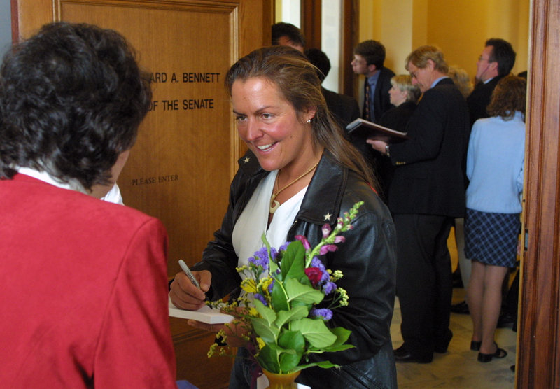 """Zoe Zanidakis signs an autograph during a visit to the State House in 2002, when she was saluted by the Legislature after being the first contestant from Maine on """"Survivor."""""""