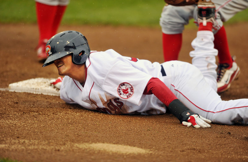 Che-Hsuan Lin dives safely back to first base Wednesday night at Hadlock Field during the Sea Dogs' 13-4 loss against the Reading Phillies.