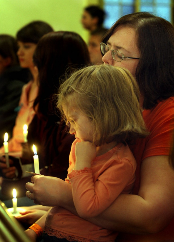 Elita Galvin and her daughter Sarah, 4, attend the vigil at First Parish Federated Church in South Berwick on Wednesday held for Camden Pierce Hughes, whose body was found in South Berwick on Saturday.