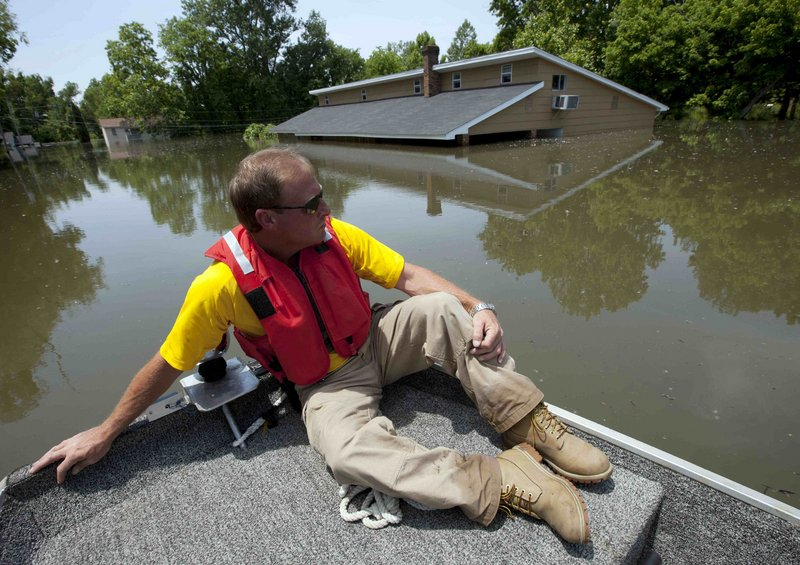 Deputy Mike Traxler views the rooftops of flooded homes in Vicksburg, Miss., Wednesday. Worries eased as floodwaters from the Mississippi River crested at Vicksburg Thursday at a slightly lower level than expected.