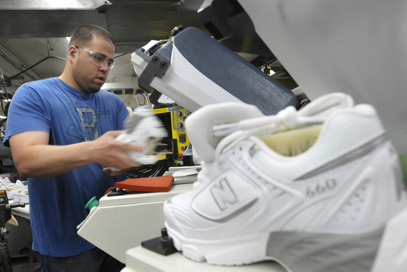 Justin Waring places soles on shoes at the New Balance plant in Norridgewock.