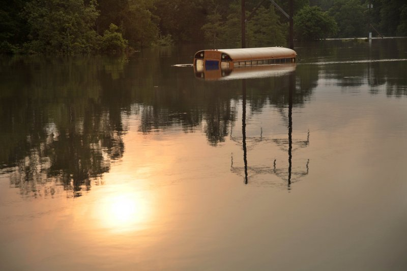 An old school bus sits in floodwaters from the rising Mississippi River in St. Francisville, La., where a dozen homes and businesses, and several camps were flooded Friday. A mandatory evacuation starts today.