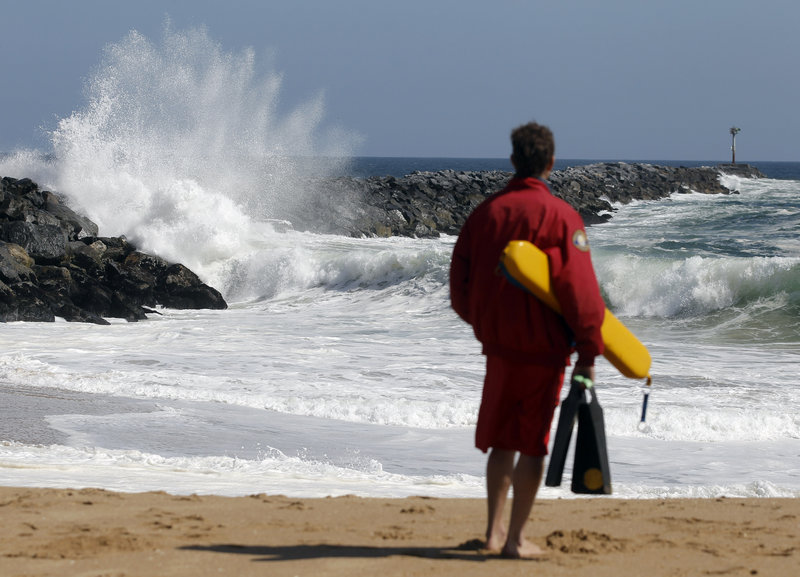 """A Newport Beach lifeguard watches the high surf at the """"Wedge"""" in Newport Beach, Calif. The local newspaper recently editorialized about high lifeguard salaries, benefits and overtime pay."""