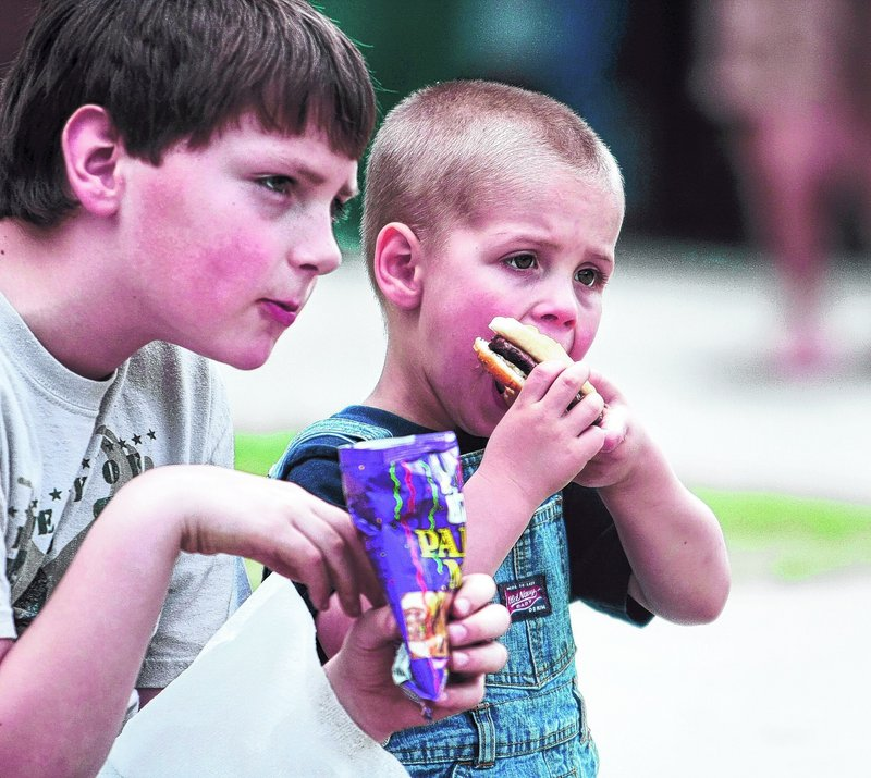Teigan Cole, 9, and his cousin Isaiah Cole, 4, take a break from the activities for lunch.