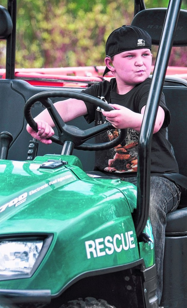 Dakotah Staples, 8, gets comfortable behind the wheel of an emergency medical services four-wheeler.