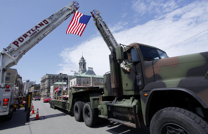 Staff Sgt. Robert Martel of Lisbon peers out of the truck carrying the beam as the convoy journeys past the Portland Fire Department on Congress Street on Saturday.