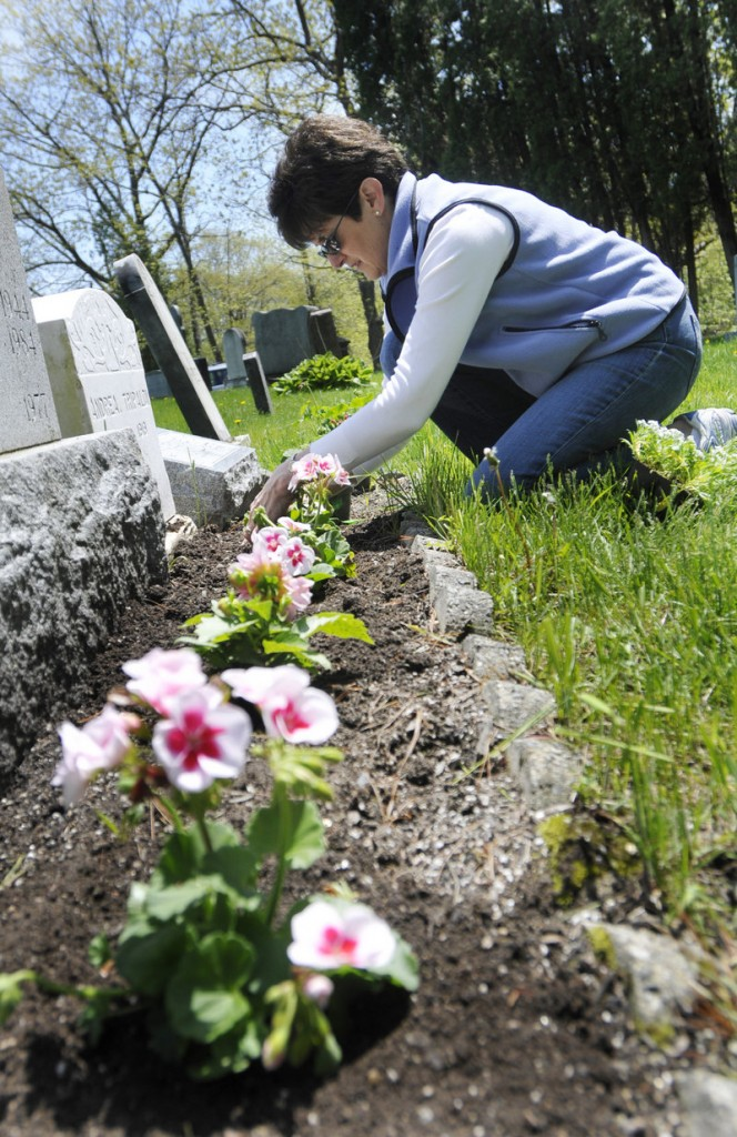 Connie Thuottle of Westford, Mass., plants geraniums in front of her grandparents' graves at Calvary Cemetery in South Portland on May 21. Thuottle is originally from South Portland.