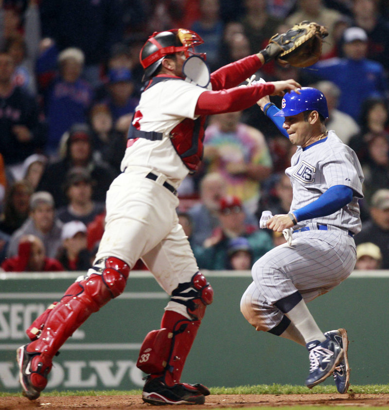 Red Sox catcher Jason Varitek reaches for a throw Saturday night as Carlos Pena crosses the plate for the Chicago Cubs after shortstop Jed Lowrie dropped a pop fly. It was all part of a horror-filled eighth inning that doomed Boston to a 9-3 loss at Fenway Park.
