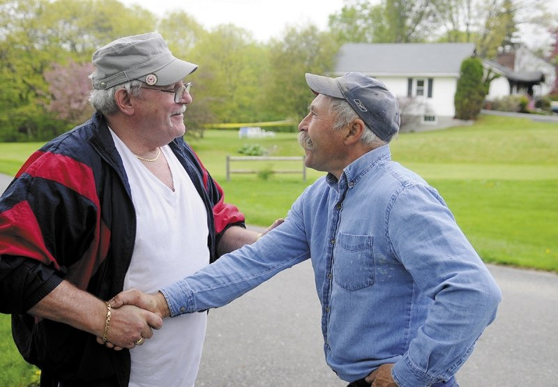 Augusta homeowner Ken Ward, left, is consoled by his friend Gary Paquette on Sunday morning. Ward's home burned down early Sunday after being struck by a pickup truck.