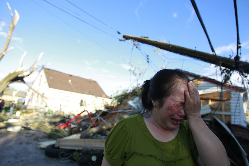 Chue Vang, 50, reacts after discovering that her Minneapolis home was damaged by a tornado Sunday.