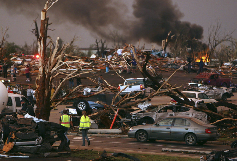 Emergency personnel walk through a neighborhood severely damaged by a tornado near the Joplin Regional Medical Center in Joplin, Mo., on Sunday. A large tornado damaged the hospital and hundreds of homes and businesses.