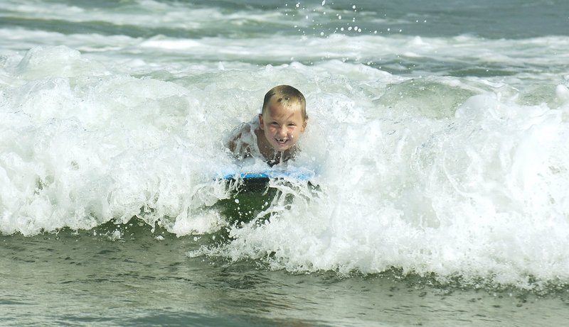 A boy beats the heat at Old Orchard Beach last summer by boogie boarding in the surf.