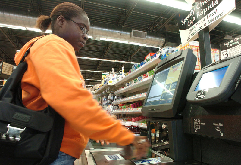 Tifany Greendge checks out her purchases at a Walmart Neighborhood grocery store in Orlando, Fla. Walmart is now taking the neighborhood grocery concept to other cities.