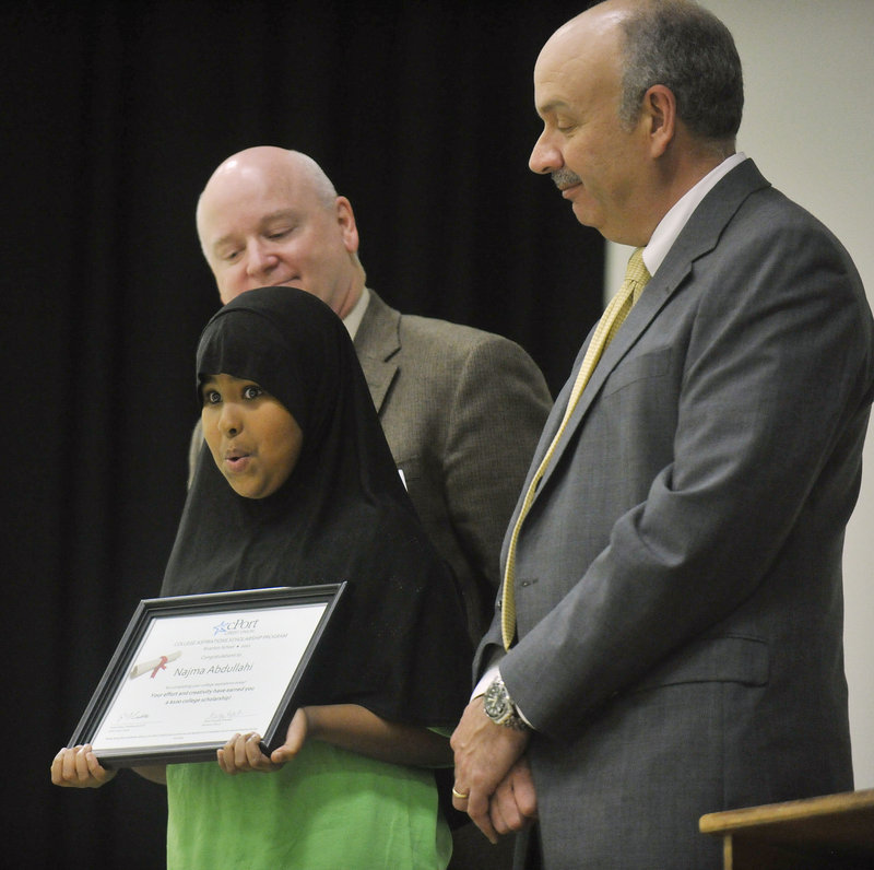 Najma Abdullahi, a fifth-grader at Riverton, holds her scholarship certificate on stage with schools Superintendent James Morse and cPort Credit Union president Gene Ardito.