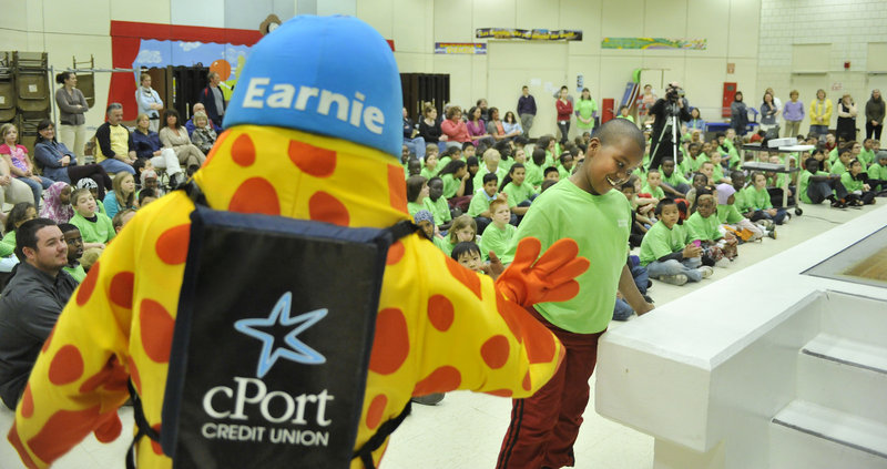 Fourth-grader Habiib Mohamed, who has ambitions to join the FBI, gets a high-five from Earnie, the cPort Credit Union mascot. CPort spent about $20,000 this year on the project, plus many hours of staff time to implement the event.