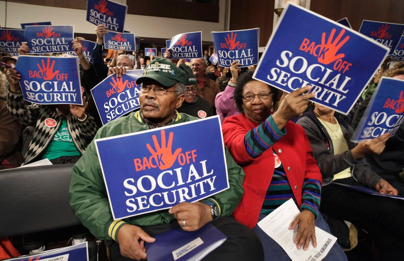 "Audience members wave signs at a ""Back Off Social Security"" rally on Capitol Hill in Washington in March. A recent poll shows that most Americans don't believe Medicare and Social Security will need to be trimmed in order to balance the federal budget."