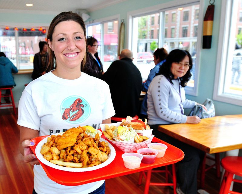 Server Kara Maxsimic serves a Fisherman's Platter (haddock, scallops, clams, french fries and coleslaw) along with a lobster roll (drawn butter, no mayo) at Portland Lobster Co., which has reopened for the season.