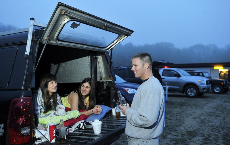 Jessica and Katlyn Irish of Windham chat comfortably with a friend, Chris Bennett of Gray, after settling in to watch a movie at the Prides Corner Drive-In on Route 302 in Westbrook. Prides Corner is one of five remaining drive-in theaters in Maine.