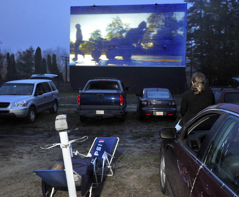 Anne Libby, 15, sits on the hood of her father's car, right, while her brother lounges in a chair as they watch a movie at the Prides Corner Drive-In in Westbrook. Movies are projected from a reel that measures nearly 3 feet across.
