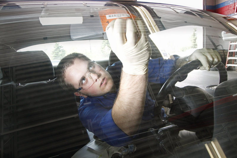 Erik Lowell, a service adviser/technician at AAA in Portland, puts a new sticker on a 1997 Nissan 240SX after he inspected and passed the vehicle Tuesday.