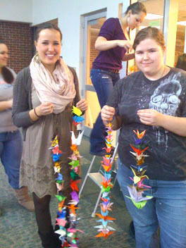 Bonny Eagle High School students Viktoria Karsten, left, and Julia Tracy help hang some of the 700 paper cranes created to raise funds to benefit Japanese disaster relief.