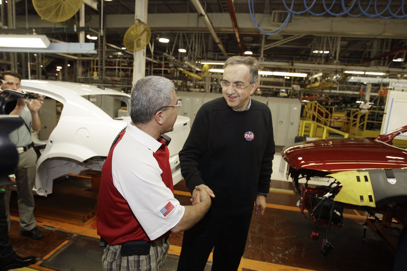 Chrysler Group CEO Sergio Marchionne, right, is greeted by Tony Al-Abawi on the assembly line Tuesday at the Sterling Heights Assembly Plant in Sterling Heights, Mich., where it was announced that the company had repaid $7.6 billion in loans.
