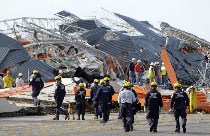 Members of the Missouri Task Force One search-and-rescue team work at a tornado-damaged Home Depot store Tuesday in Joplin, Mo. A day earlier, rescuers found one person alive in the store's wreckage but also recovered seven bodies under the concrete.
