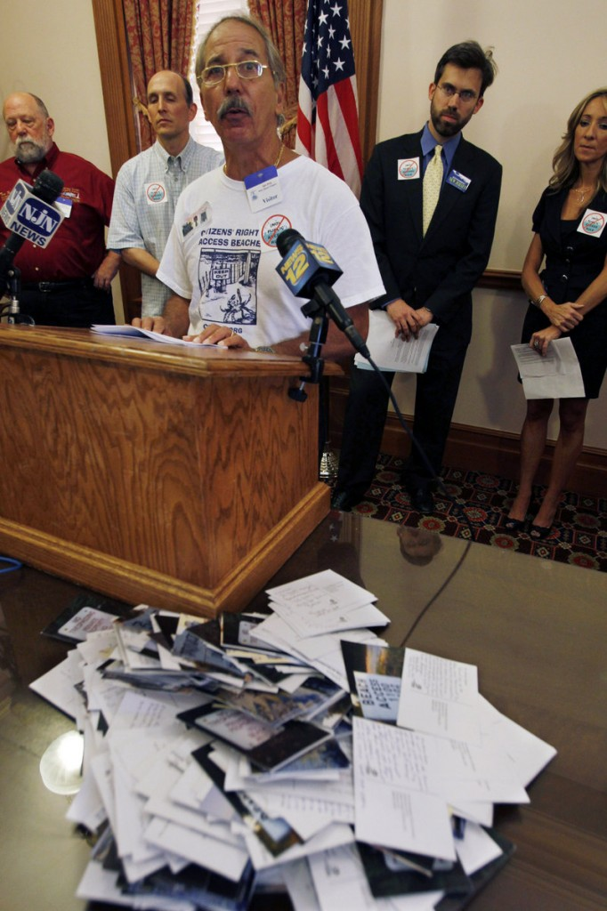 "Ralph Coscia of Point Pleasant Beach, N.J., stands near a pile of ""Dear Gov. Christie"" postcards from opponents of New Jersey's proposed beach access rules, on Wednesday in Trenton."