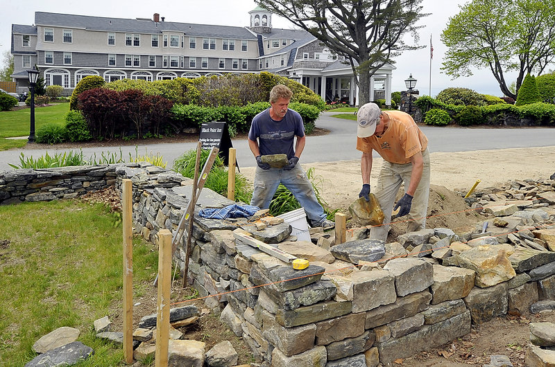 A stone wall takes shape Thursday at the Black Point Inn in Scarborough. Ted Wheeler, left, helps John Lord, owner of JS Lord Masonry of Naples, build the wall. The Memorial Day weekend is expected to be a busy period for the inn.
