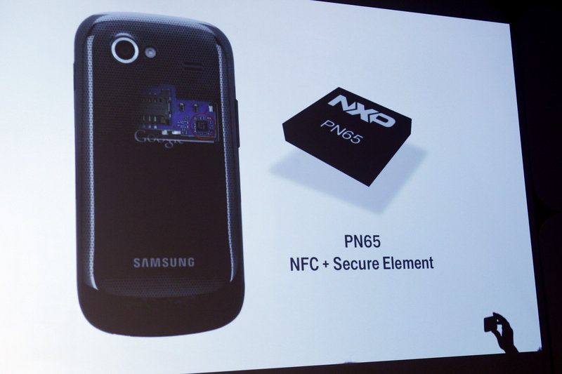 A security chip is displayed on a screen during the presentation.