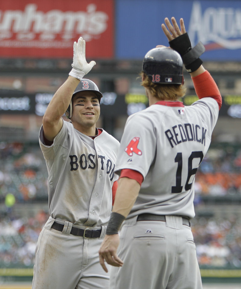 Jacoby Ellsbury, left, is greeted at home plate by Josh Reddick after hitting a three-run home run Thursday in the second inning of Boston's 14-1 win over the Tigers at Detroit.
