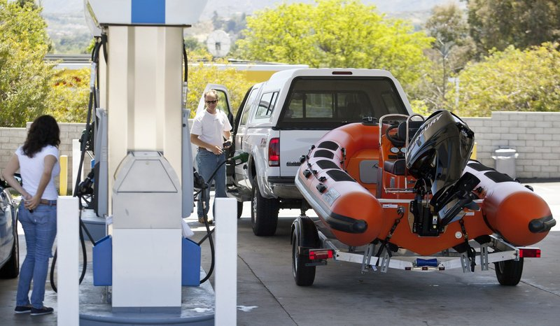 Travelers fill up their tanks at a gas station for an early start on the Memorial Day weekend traffic in Valencia, Calif., on Friday. Gas prices still topping the $4-a-gallon mark in much of the country are forcing motorists to spend more on fill-ups and doing more complicated math to make the summer budget work.