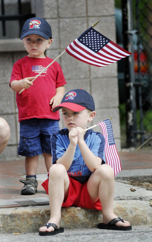 Reid Haile, 2, left, and Henry Haile, 5, of Westbrook show their patriotic spirit as they watch the Memorial Day parade in Portland on Monday.