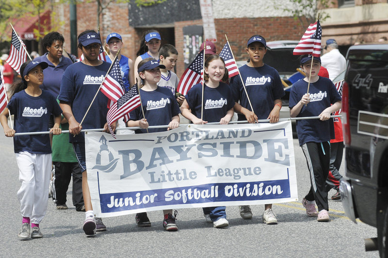 A local softball league is represented by some flag-waving players Monday. The parade included color guards from veterans organizations, bands from Portland and Deering high schools, a flotilla of pageant queens, and Scout groups.