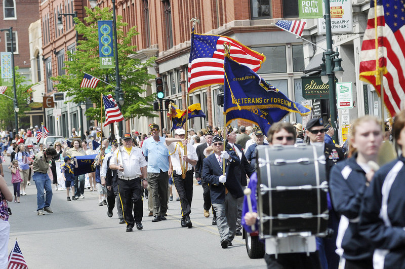 Veterans and marching bands parade down Congress Street in Portland on Monday.