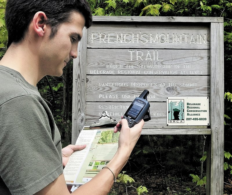 Joel Alex checks his GPS unit for a kiosk sign at the head of a trail leading to French's Mountain in Rome.