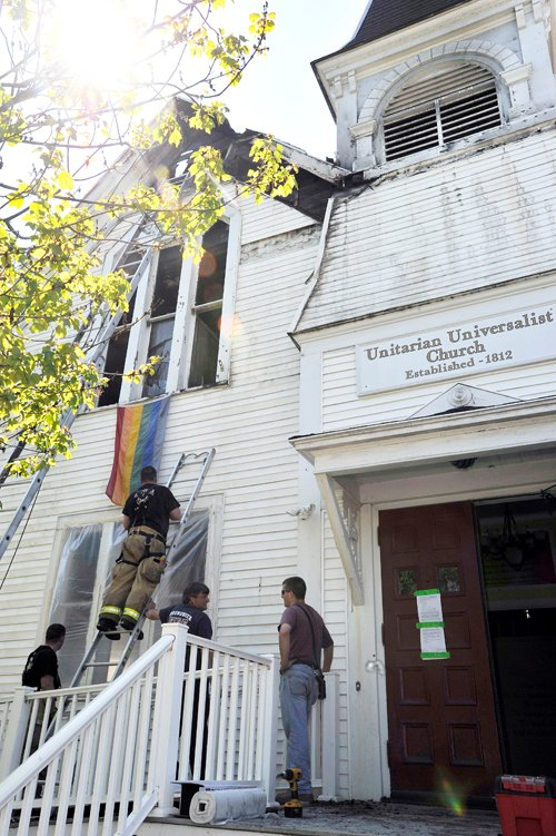 Brunswick firefighters cover damaged windows in the aftermath of an early morning fire at the Unitarian Universalist Church on Pleasant Street in Brunswick.